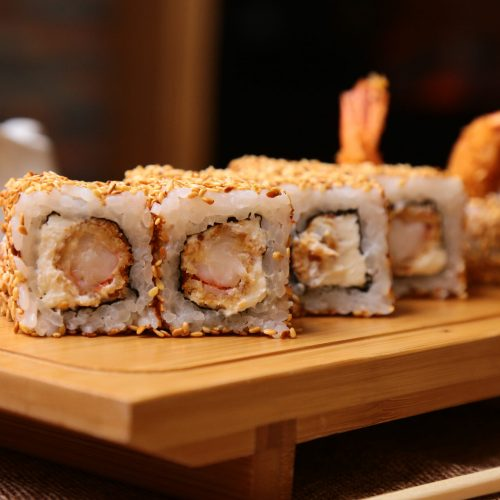 side view of traditional japanese cuisine sushi roll with rice shrimps and cream cheese and seasame on a wooden board