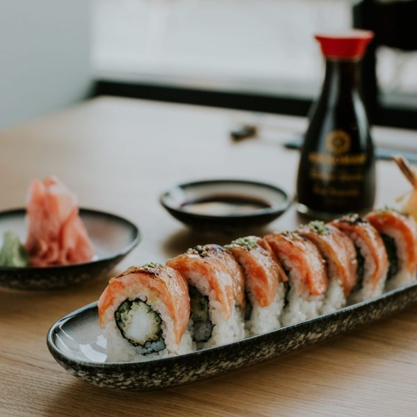 High angle shot of a plate with sushi and its ingredients on a table with blurred background